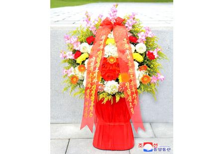 김일성 동지와 김정일 동지의 동상에 공화국영웅유가족 꽃바구니 진정