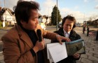 Kim Joo-il (l) and Jung Su-ban hold up a book of North Korean photographs outsied the DPRK Embassy