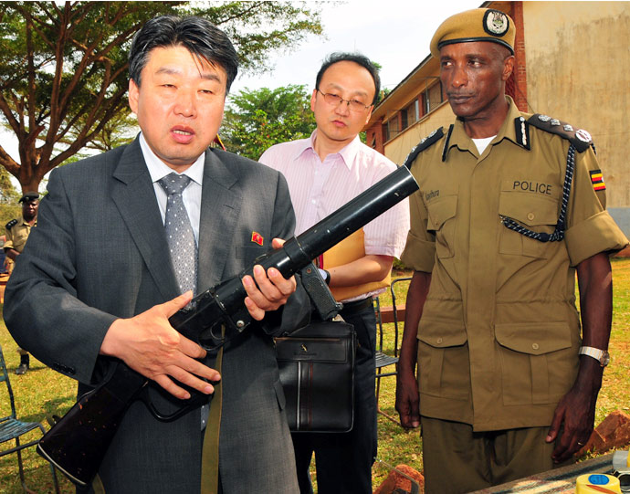 North Korean Vice Minister for People's Security, Ri Song Chol, left, with Uganda's Inspector General of Police, Gen. Kale Kayihura, right, inspects a Uganda Police officer loading a tear gas can into a launcher in Kampala during a five day visit to Uganda, Tuesday 11 June, 2013. | Picture: Stephen Wandera for NK News
