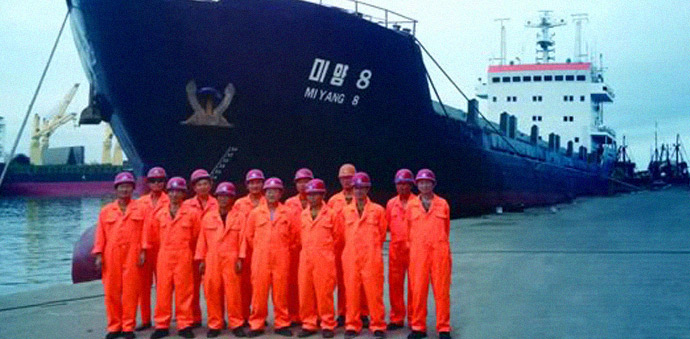 Dalian Global Unity (GU) Shipping employees stand in front of the 'Miyang 8', a container ship that regularly travels between Dalian and the North Korean port city of Nampho. (Photo: GU Shipping)