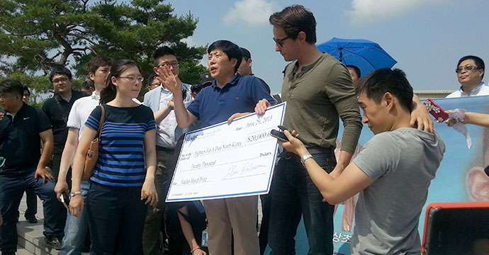 Thor Halvorssen of the Human Rights Foundation and Oslo Freedom Forum awards Park Sang-hak with the $20,000 prize money for 'Creative Dissent'. Photo: Hyowon Shin, NK News.