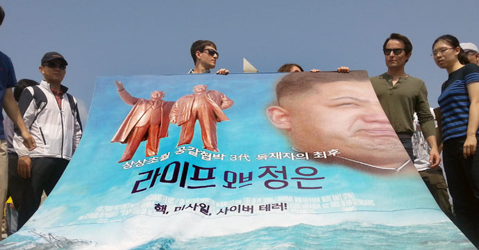 "Members of the Human Rights Foundation and Freedom Fighters for North Korea hold up a satirical poster showing Kim Jong Un's ""Life of Pi"". Photo: Hyowon Shin, NK News."