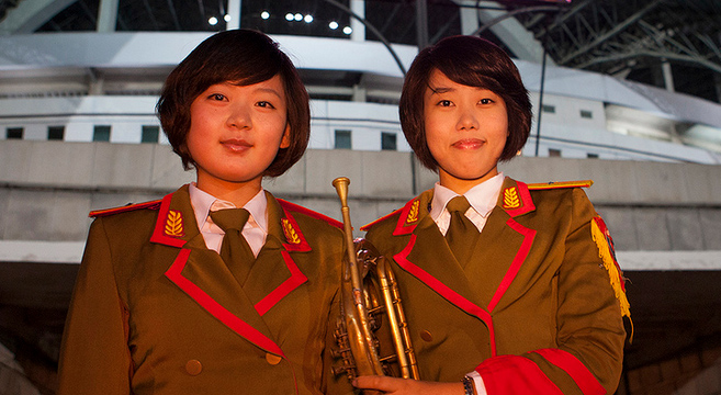 Two female North Koreans stand outside the May Day Stadium in Pyongyang | Picture: E. Lafforgue