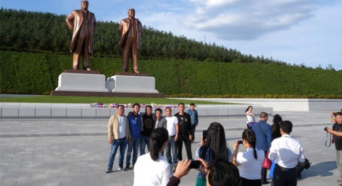 Chinese tourists pose next to statues of Kim Il Sung and Kim Jong Il | Picture: NK News