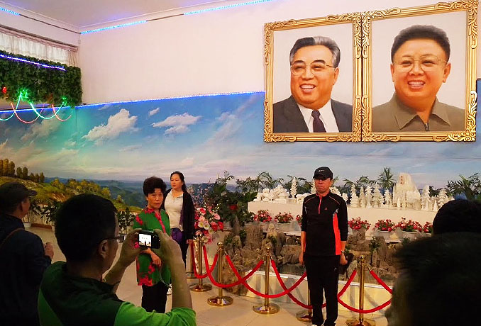 Chinese tourist poses in front of portraits of the two Kims | Picture: NK News