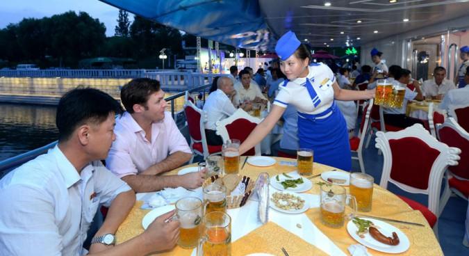 North Korean waitress clad in uniform serves beer to foreigner at the beer festival Image credit: Uriminzokkiri