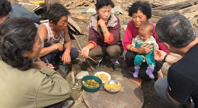 A Korean family eats a meal in the rubble of their destroyed house I Credit: Murat Sahin in UNICEF DPRK