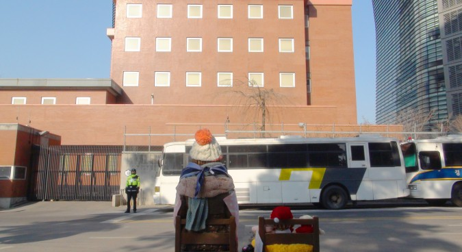 japanese_embassy_in_seoul_and_watched_from_behind_a_bronze_statue_of_comfort_women